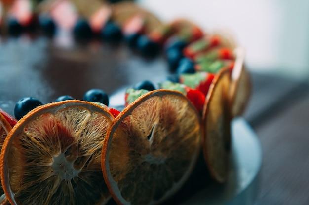 신선한 딸기 민트 설탕에 절인 오렌지로 장식된 맛있는 초콜릿 케이크의 거시적 전망
