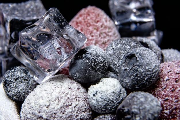 冷凍ベリーのマクロの表示:暗い背景にアイスキューブとイチゴ、ブルーベリー