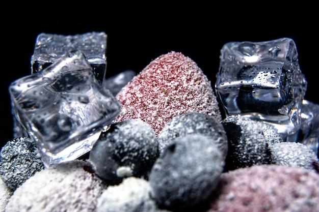 Макрос вид замороженных ягод: клубника, черника с кубиками льда на темном фоне