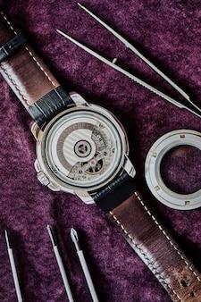 보라색 스웨이드에 수리 대기 중인 가죽 스트랩에 자동차 공장이 있는 손목시계 메커니즘의 매크로 보기, 위쪽