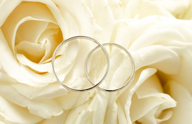 Macro view of two wedding rings lying on bridal bouquet