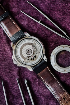 Macro view of wristwatch mechanism with car factory on leather strap pending repair on purple suede, top view