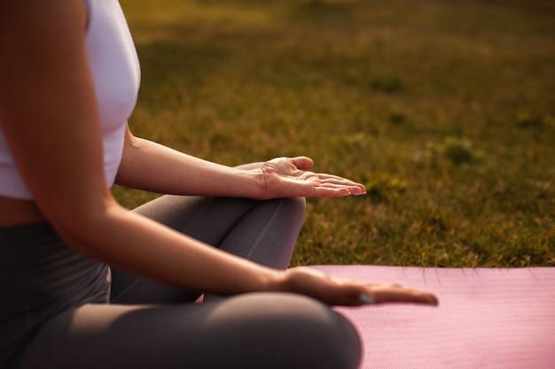 거시적인 여성은 명상 포즈, 내면의 평화와 정신 건강의 개념으로 손바닥을 엽니다.