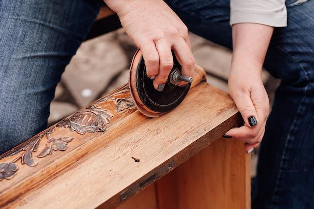 Макро женские руки шлифуют старую деревянную коробку с цветочным узором, удаляя старую полировку и препарин ...