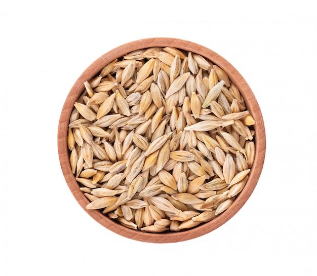 Солодовые зерна ячменя в деревянной миске, изолированные. семена ячменя заделывают. вид сверху. macro.