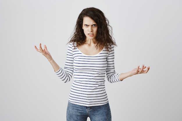 Сумасшедшая и раздраженная женщина жалуется, пожимает руки и хмурится