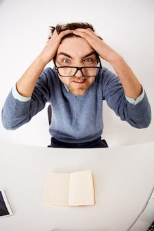 マッドで苦しめられた若いプレッシャーをかけられた男、ツアールの髪と仕事として怒っている顔をゆがめた、机に座ってアイデアを考えることができない