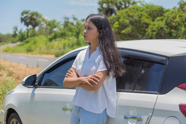 Mad asian girl standing at the car on the street