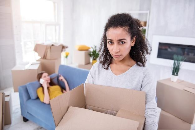 あなたに怒る。ルームメイトがソファに横になって電話でおしゃべりしながら、イライラした表情でカメラを見て重い箱を運ぶ縮れ毛の少女