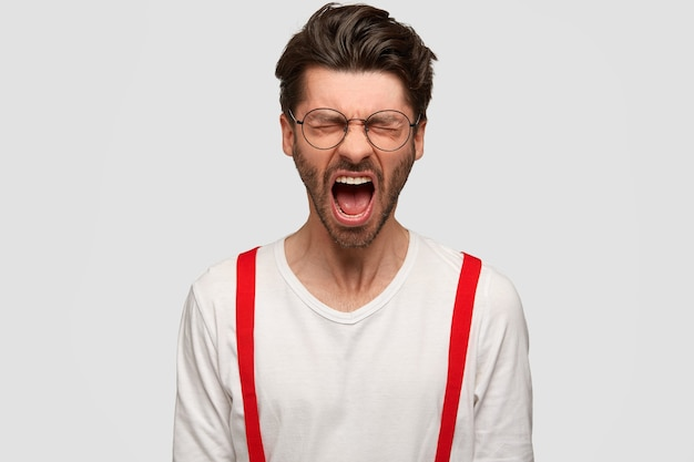 Mad bearded man screams angrily, opens mouth widely, closes eyes with displeasure, expresses negative emotions, stands against white wall. furious irritated boss shouts at colleagues.