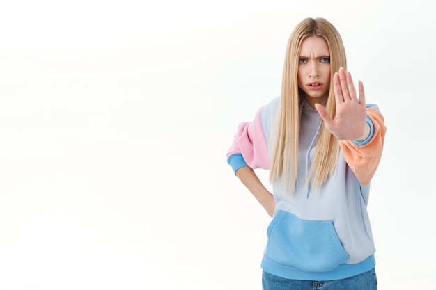 Mad blonde girl with long hair, colored hoodie, outward arm to front, saying stop, prohibit action, warning someone disagree