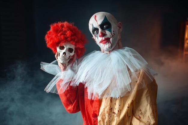 Безумный кровавый клоун держит человеческий череп в красном парике