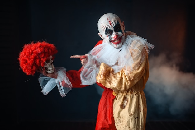 Mad bloody clown holds human skull in red wig, horror. man with makeup in carnival costume, crazy maniac