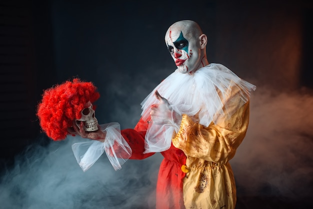Mad bloody clown holds human skull in red wig