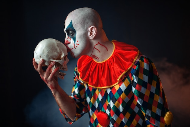 Mad bloody clown holds human skull