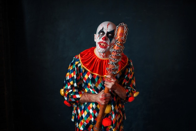 Mad bloody clown with baseball bat. man with makeup in halloween costume, zombie