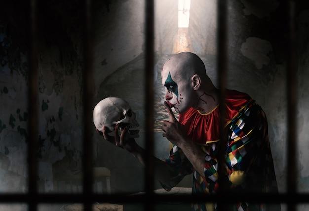 인간의 두개골을 가진 미친 피투성이 광대는 조용한 표시, 끔찍한 비밀을 보여줍니다. 카니발 의상, 미친 미치광이 메이크업을 가진 남자