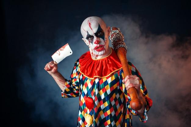 肉切り包丁と野球のバット、サーカスの恐怖を持つ狂った血の道化師。狂気のマニアックなカーニバル衣装で化粧品を持つ男