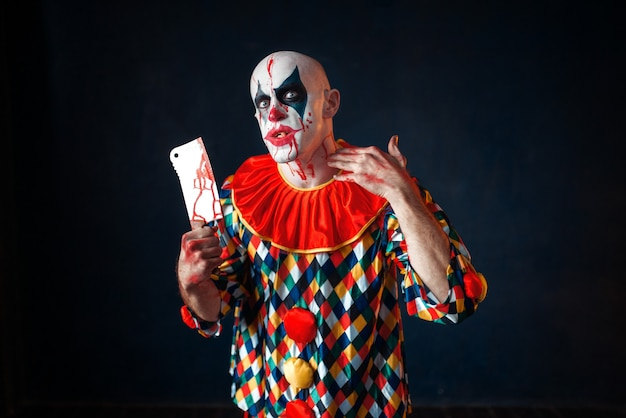 Mad bloody clown with meat cleaver, circus horror. man with makeup in carnival costume, crazy maniac