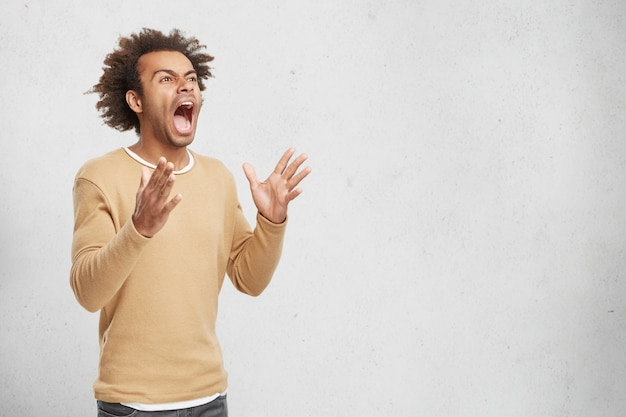Mad crazy desperate man screams loudly in panic, gestures with hands