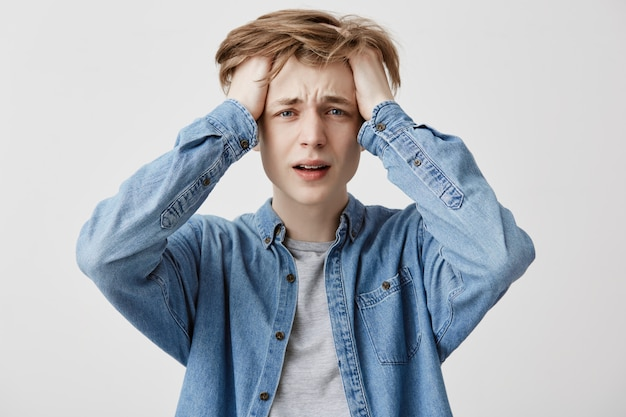 Mad crazy upset guy regrets about mistakes, dressed in denim shirt, understands that he can`t change anything or return time back to improve situation, being in panic and stress. great desperation