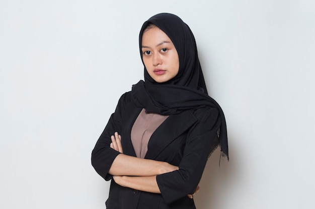 Mad face asian muslim woman in head scarf smile with arms crossed