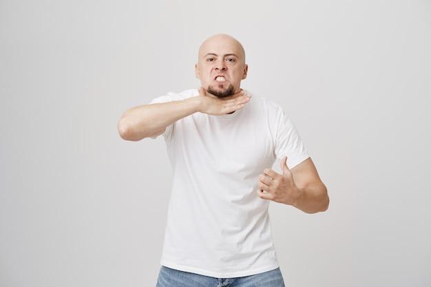 Безумный сытый по горло лысый мужчина угрожает, перерезает горло жестом