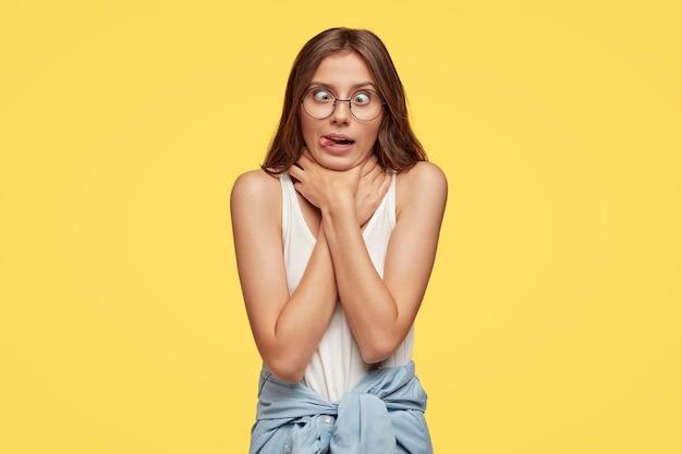 Безумная смешная девчонка имитирует самоубийство или астматический припадок, держит руки на шее, скрещивает глаза и показывает язык, дурачит в помещении