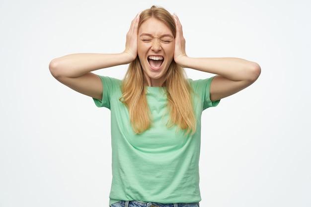 目を閉じてミントのtシャツにそばかすのある狂った猛烈な女性は、手で耳を円錐形にし、白で叫んでいます