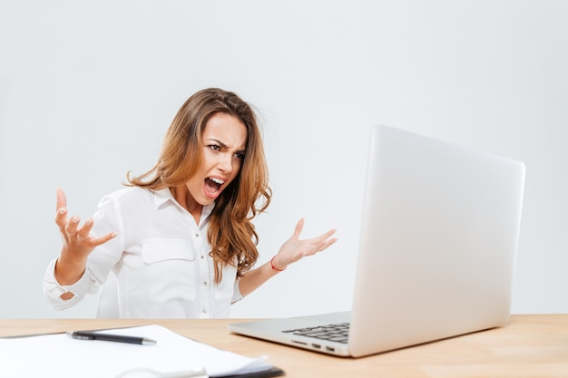 Mad furious young businesswoman using laptop and screaming over white background
