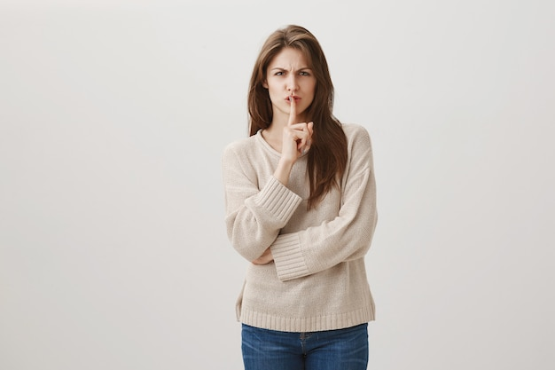 Mad grimacing woman tell be quiet, shushing at person