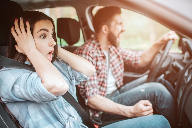 Mad guy and amazed girl are stopping unexpectedly. guy is screaming while girl is holding her hands near ears and looking on road.