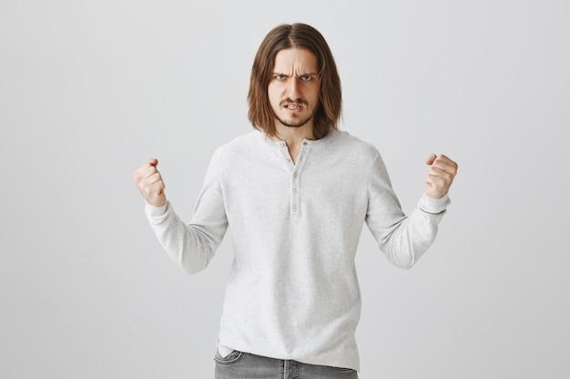 Сумасшедший парень сжимает кулаки в гневе и выглядит решительным