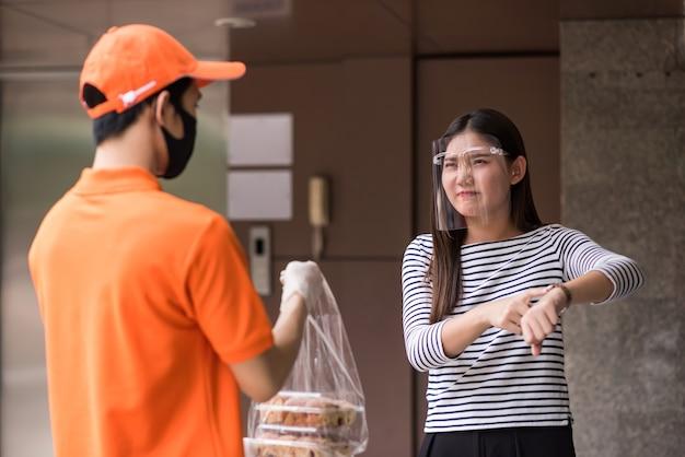 얼굴 가리개를 한 미친 배고픈 아시아 여성이 음식 지연에 대해 불평하기 위해 시계를 보여줍니다. 마스크를 쓴 택배 배달원은 업무량으로 인해 후회하거나 미안하다. covid-19 보호와 함께 사무실에서 굶주린 소녀