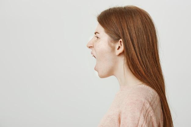 Безумная рыжая женщина, стоящая в профиль и кричащая сердито