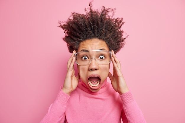 狂ったショックを受けた女性が大声で恐怖を見つめ、口を大きく開いたままにします髪を立てて透明なメガネをかけますカジュアルなタートルネック