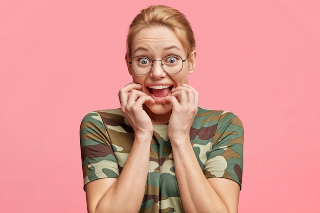 Mad surprised female model with eyes popped out, stares through round spectacles, bites finger nails, feels nervous and excited, reacts on something very actively, isolated over pink