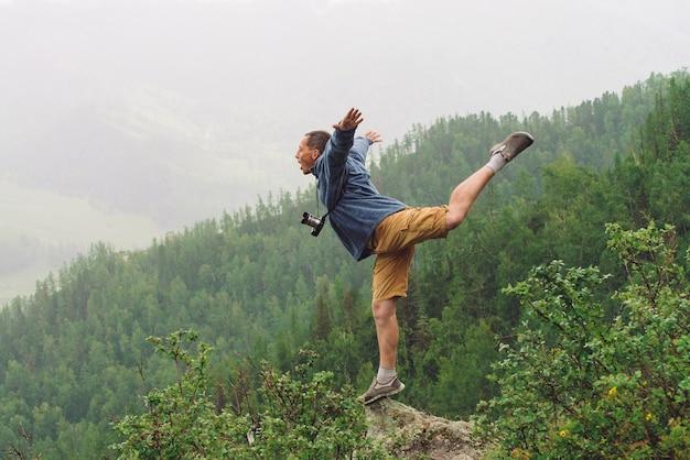 Mad tourist on mountain peak.
