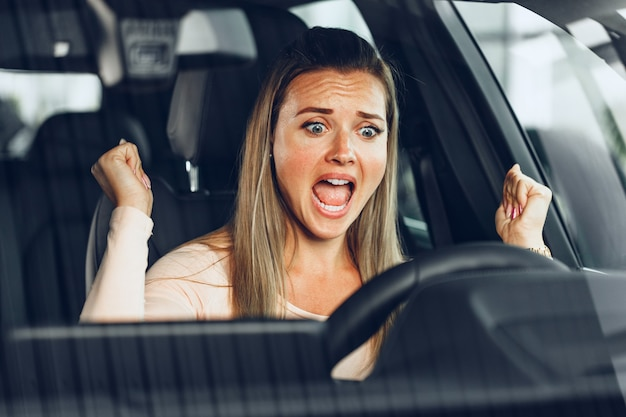 Mad woman driving a car stuck in a traffic jam
