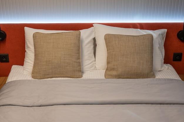 ベッドと茶色の枕を作りました。ホテルの部屋の化粧ベッドのクローズアップ。部屋の清潔な寝具、枕、ベッドシーツ、毛布。インテリアデザインのクローズアップ。