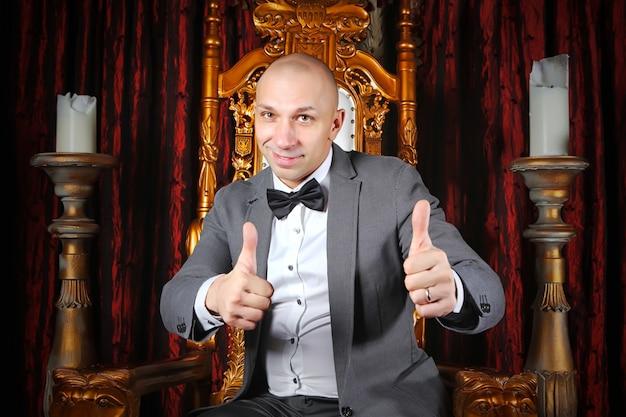 Сделанный бизнесмен показывает палец вверх знак, что ему нравится или одобряет что-то на троне в интерьере фона. понятие о хорошем бизнесе. шоумен и показывает палец вверх. авторские права