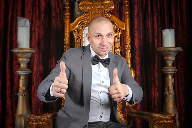 Сделанный бизнесмен показывает палец вверх знак, что ему нравится или одобряет что-то на троне в интерьере фона. шоумен и показывает палец вверх. место для надписи или логотипа