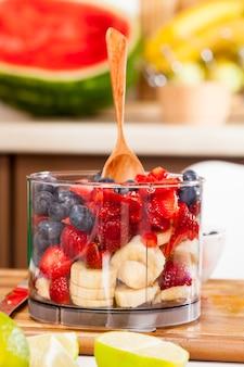 Приготовленный из разных видов ягодных смузи, смузи состоит из клубники, черники и черники с добавлением кусочков банана и арбуза.