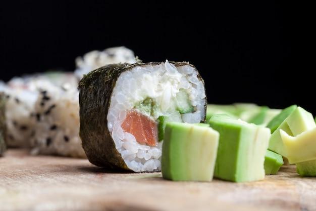 Сделано из риса и форели или лосося с овощами, суши, азиатский рис и морепродукты на столе во время еды, азиатские блюда