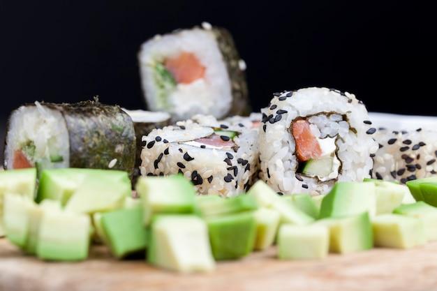 Сделано из риса с форелью и суши-овощей, азиатского риса и морепродуктов на столе во время еды.