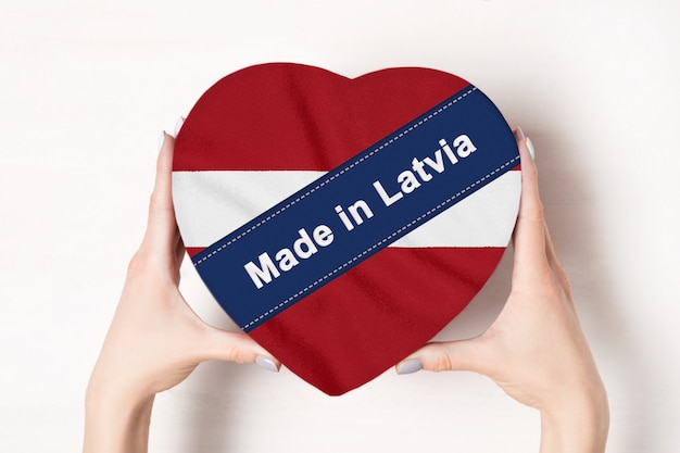 Надпись made in latvia, флаг латвии. женские руки, держа коробку в форме сердца. ,