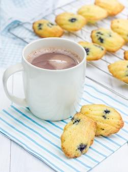 ブルーベリーとホットチョコレートのカップとマドレーヌ