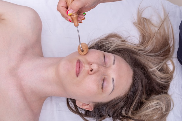 Madero therapy, anti-aging relaxing massage - hands massaging the girl's cheek using a natural wooden massager. face lifting massage, correction and removal of mimic wrinkles