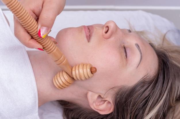 Мадеро-терапия, антивозрастной расслабляющий массаж - руки массируют шею девушки натуральным деревянным массажером. лифтинг-массаж лица, коррекция и удаление мимических морщин