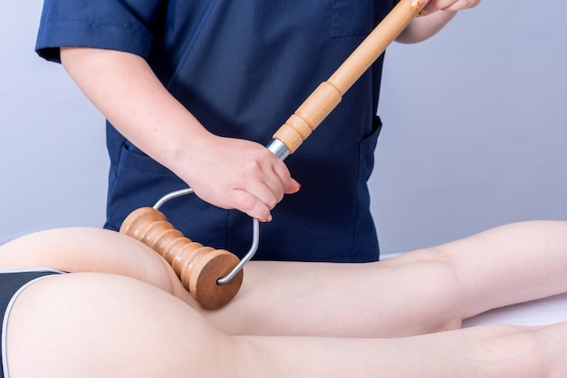 Madero therapy anti-cellulite massage, lymphatic drainage massage - woman having spa massage of the back of the thigh in a beauty salon using a wooden roller massager. body care concept